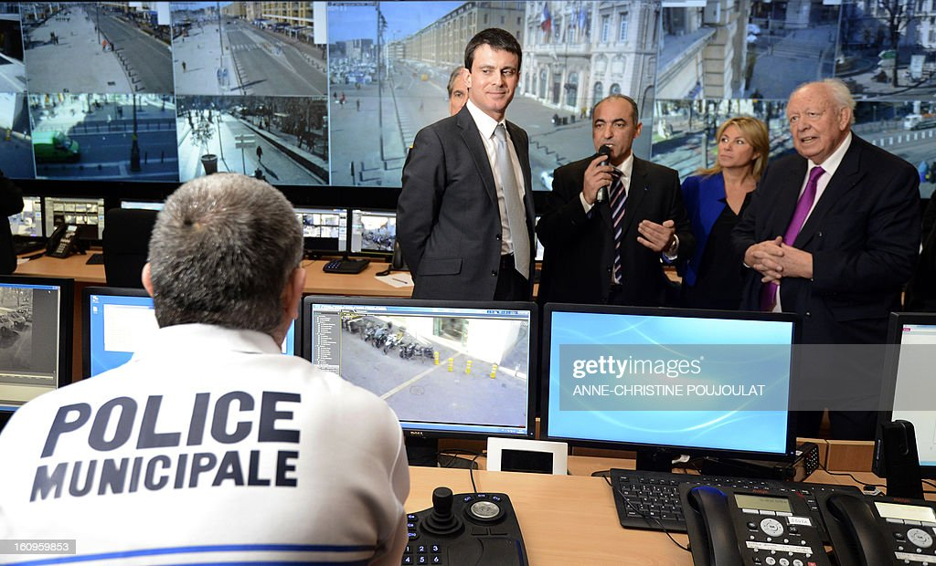 France's Interior Minister Manuel Valls (C) listens to Marseille's mayor Jean-Claude Gaudin (R) visits the real-time protection video operating room during the inauguration of the Urban Supervision Centre (CSU) on February 8, 2013 in Marseille, southern France. AFP PHOTO / ANNE-CHRISTINE POUJOULAT
