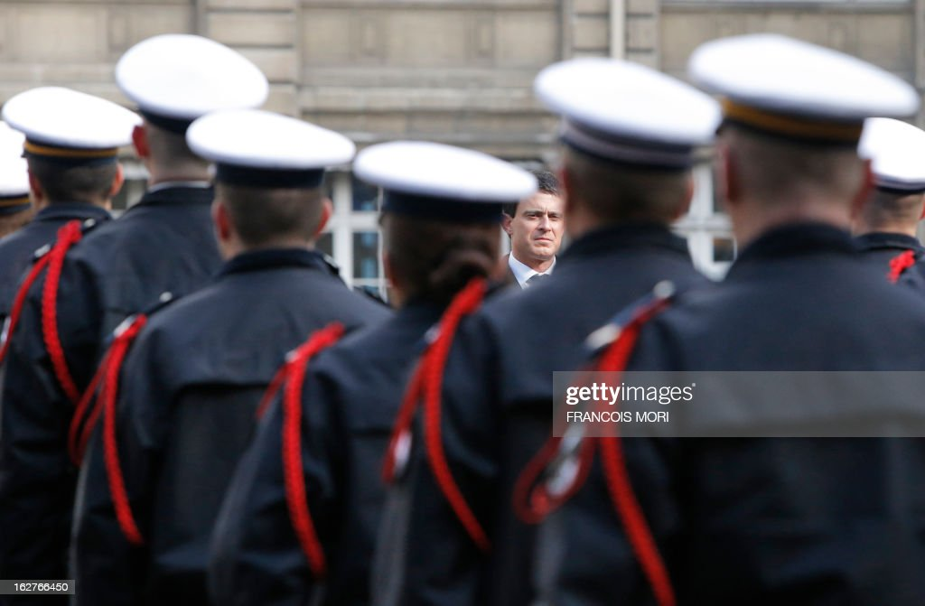 France's Interior Minister Manuel Valls (C) pays homage to the two slain policemen, during a ceremony in the yard of the Paris police prefecture, on February 26, 2013 in Paris. An alleged drunk driver killed the two Paris police officers after slamming his black Land Rover into their cruiser during a high-speed chase on the ring road around Paris.
