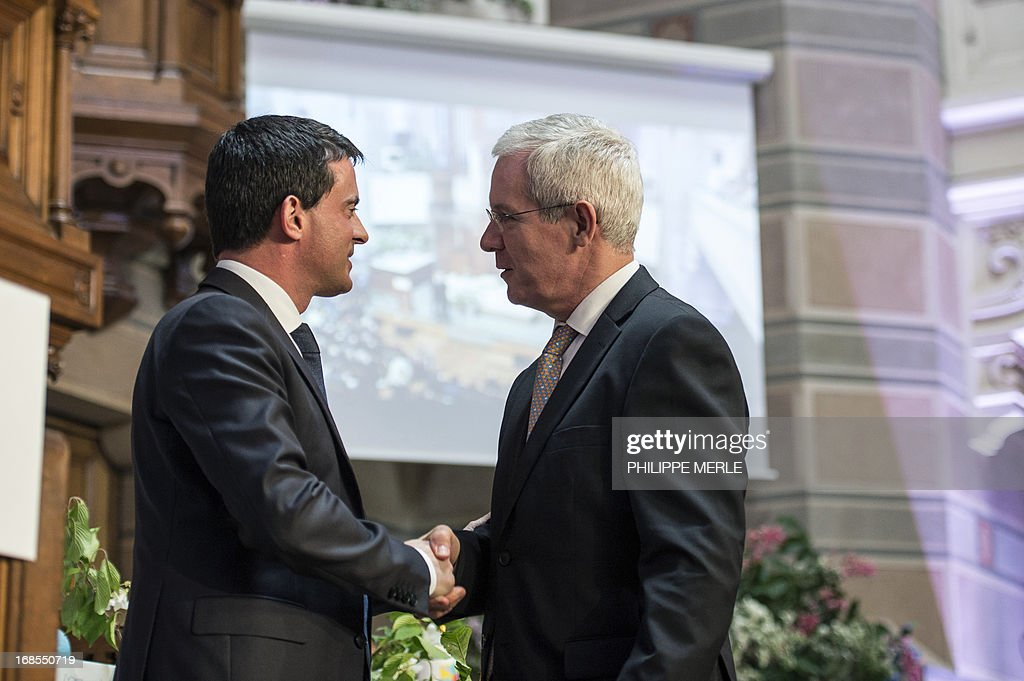 France's Interior minister manuel Valls (L) salutes newly elected president of the French council of reformed church, pastor Laurent Schlumberger, during the first national synod of the United Protestant Church of France on May 11, 2013 at the Grand Temple in Lyon.
