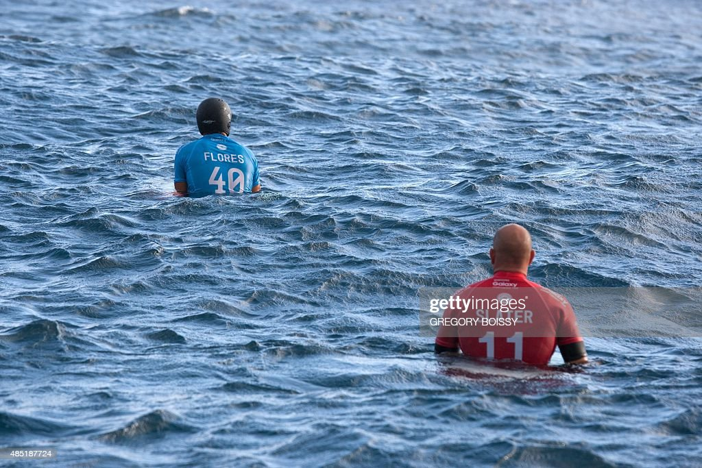France's Jeremy Flores wearing a protective helmet and USA's Kelly Slater sit on their boards in the waiting zone before the start of the World Surf...