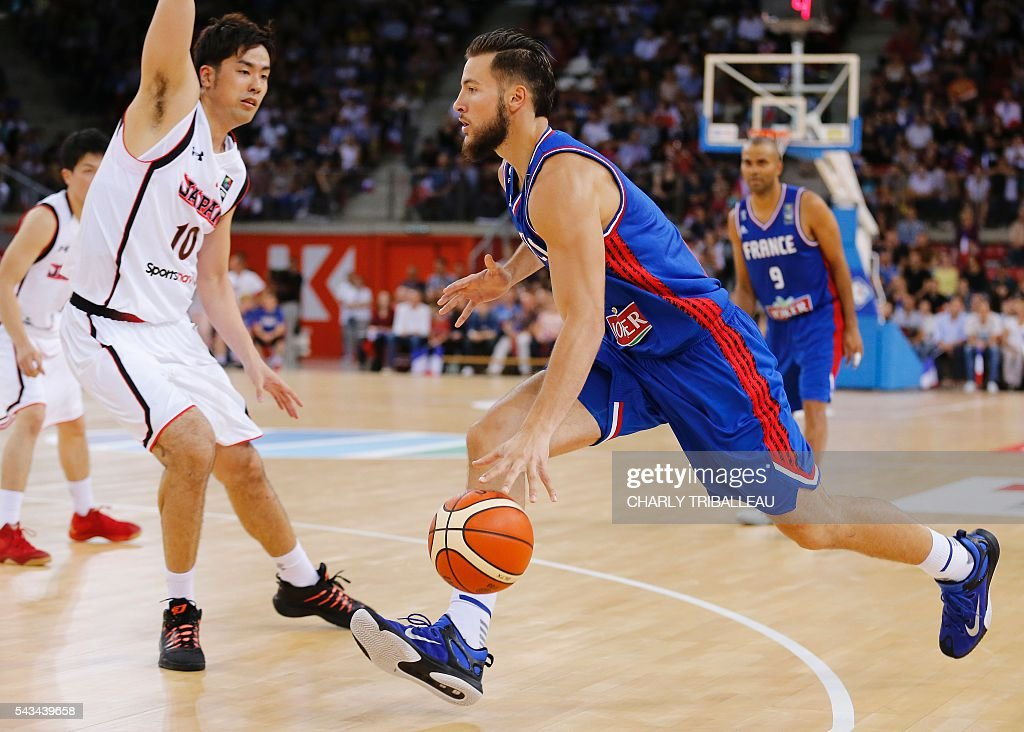 France's Joffrey Lauvergne (R) vies for the ball with Japan's Kosuke Takeuchi (L) during the basketball match between France and Japan at the Kindarena hall in Rouen on June 28, 2016. / AFP / CHARLY