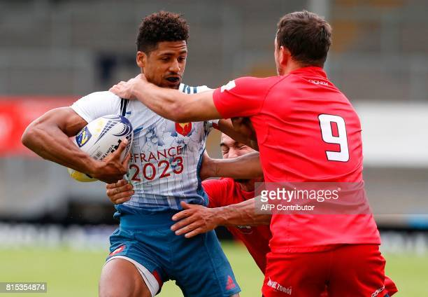 Frances Josias Daoudou is tackled by Poland's Symon Sirocki and Poland's Mateusz Matyjak during the rugby union sevens game between France and Poland...