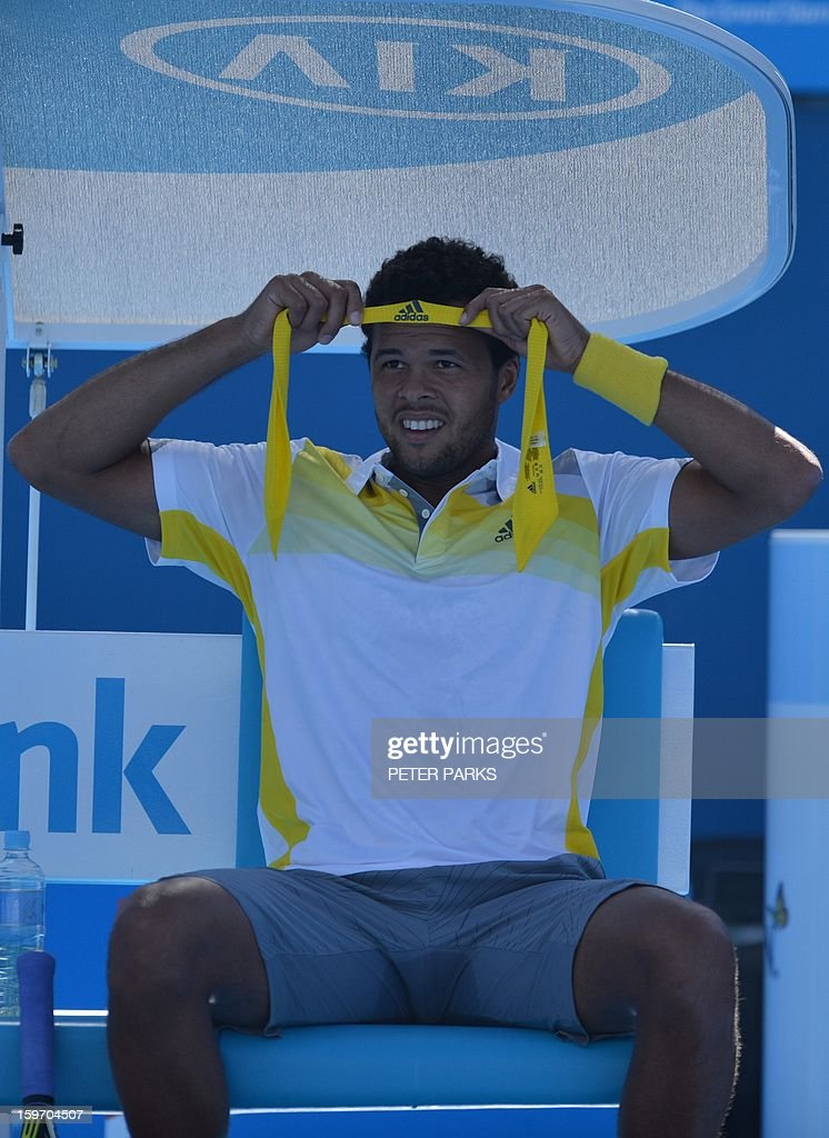 France's Jo-Wilfried Tsonga adjusts his headband during a men's singles match against Slovenia's Blaz Kavcic on day six of the Australian Open tennis tournament in Melbourne on January 19, 2013.