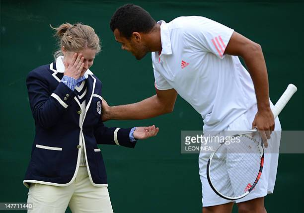 France's JoWilfried Tsonga attends to a line judge who has been hit in the face by a ball during his fourth round men's singles match against US...