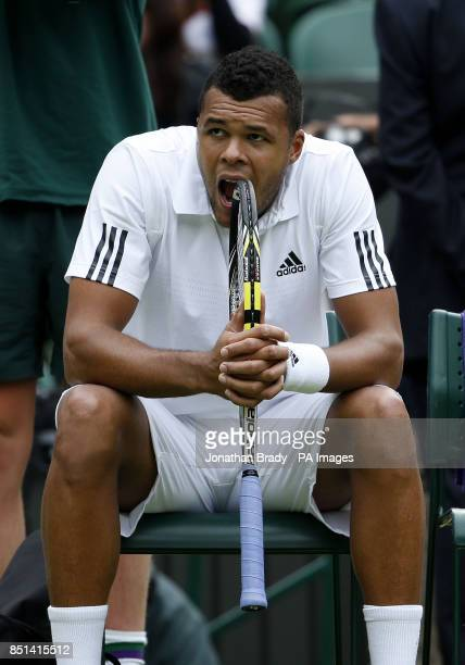 France's JoWilfried Tsonga bites his racquet during a break in his match against Latvia's Ernests Gulbis during day Three of the Wimbledon...