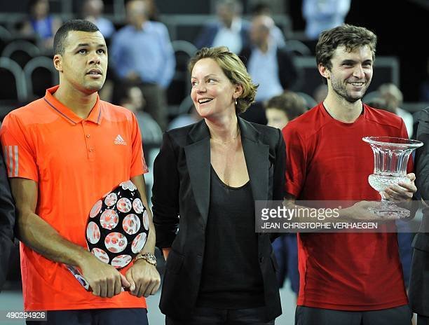 France's JoWilfried Tsonga flanked by French TV host Cendrine Dominguez holds his trophy after defeating France's Gilles Simon during the ATP Moselle...