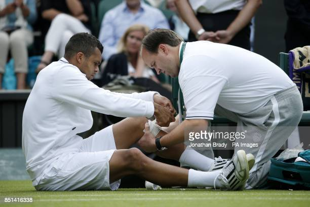 France's JoWilfried Tsonga has his leg strapped up in his match against Latvia's Ernests Gulbis during day Three of the Wimbledon Championships at...