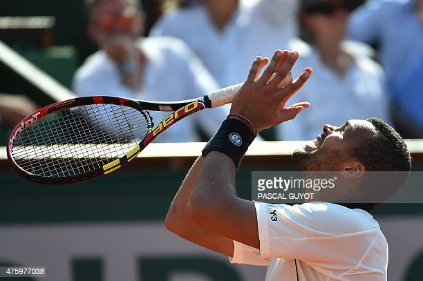 France's JoWilfried Tsonga reacts after a point against Switzerland's Stanislas Wawrinka during their men's semifinal match of the Roland Garros 2015...