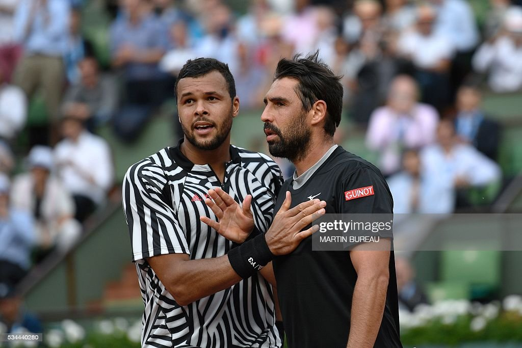 France's Jo-Wilfried Tsonga (L) shakes hands with Cyprus' Marcos Baghdatis after winning their men's second round match at the Roland Garros 2016 French Tennis Open in Paris on May 26, 2016. / AFP / Martin BUREAU