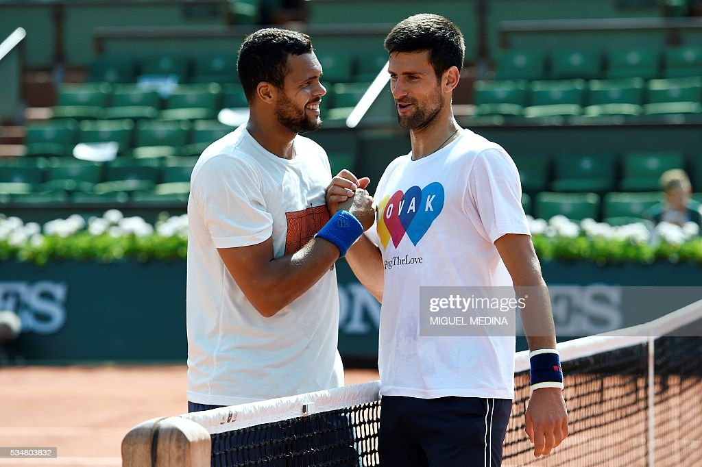 France's Jo-Wilfried Tsonga shakes hands with Serbia's Novak Djokovic after their training session at the Roland Garros 2016 French Tennis Open in Paris on May 28, 2016. / AFP / MIGUEL