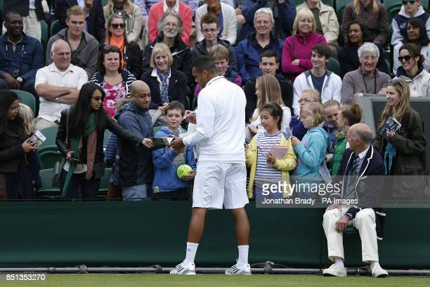 France's JoWilfried Tsonga signs autographs for fans after his match against Belgium's David Goffin during day one of the Wimbledon Championships at...