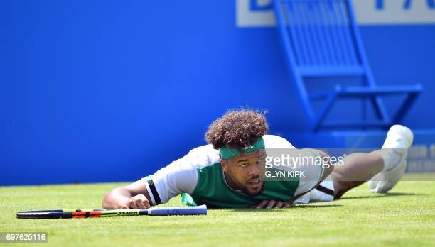 TOPSHOT France's JoWilfried Tsonga slips against France's Adrian Mannarino in their men's singles 1st round match at the ATP Aegon Championships...