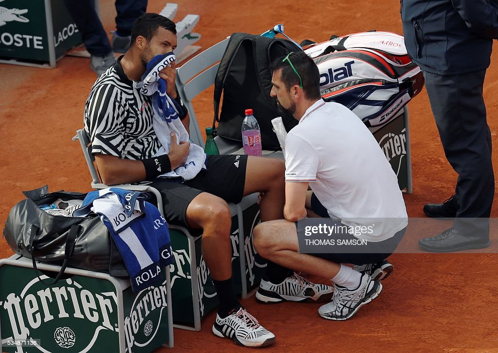 France's Jo-Wilfried Tsonga speaks with a doctor during his men's third round match against Latvia's Ernests Gulbis at the Roland Garros 2016 French Tennis Open in Paris on May 28, 2016. / AFP / Thomas SAMSON