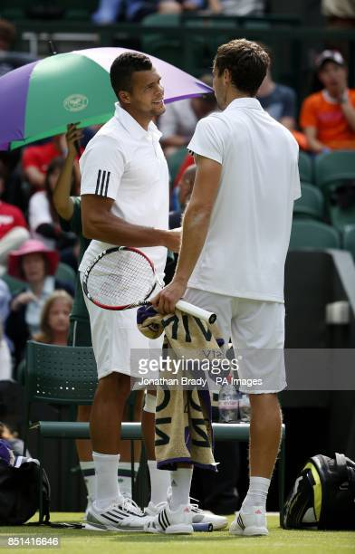 France's JoWilfried Tsonga with Latvia's Ernests Gulbis after retiring from the match during day Three of the Wimbledon Championships at The All...
