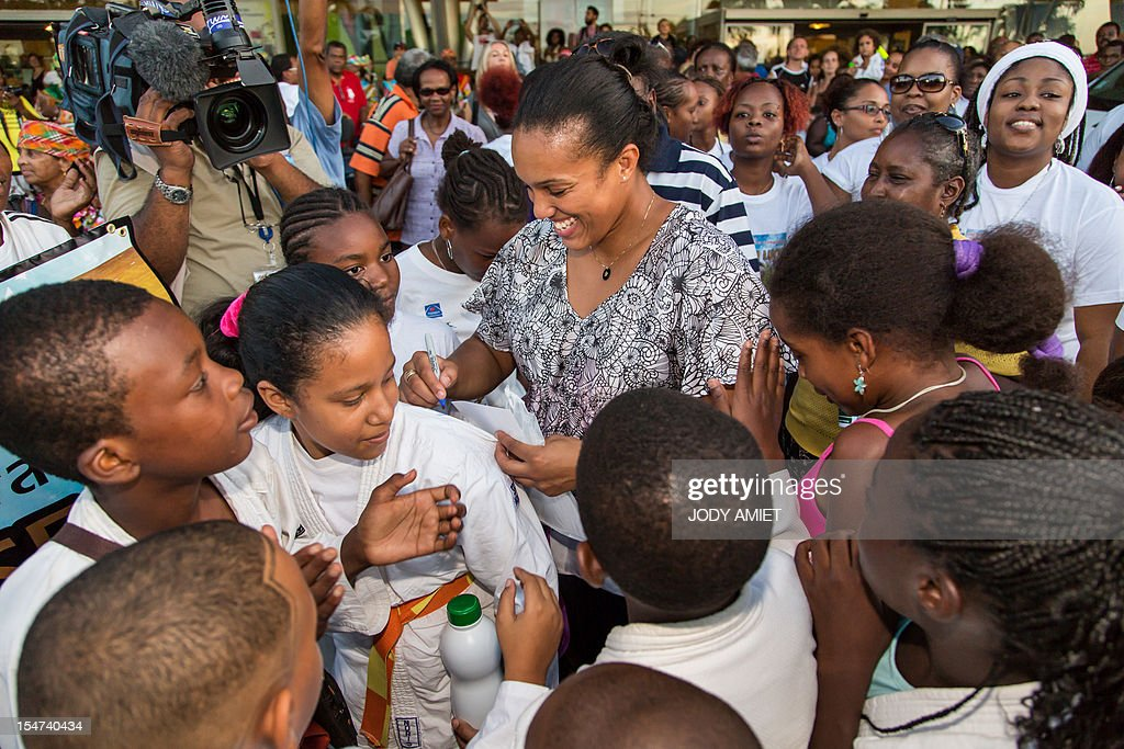 France's judo athlete and 2012 Olympic Games gold medalist Lucie Decosse (C) signs autographs as she is welcomed by supporters on October 24, 2012 in Cayenne, French overseas region of Guiana. The 30-year-old world champion beat German outsider Kerstin Thiele in the final of the women's -70kg judo contest match of the London 2012 Olympic Games on August 1, 2012. AFP PHOTO / JODY AMIET