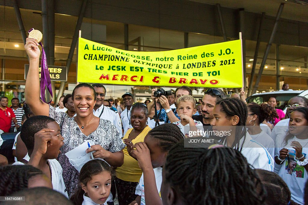 France's judo athlete and 2012 Olympic Games gold medalist Lucie Decosse (L) shows her medal as she is welcomed by supporters on October 24, 2012 in Cayenne, French overseas region of Guiana. The 30-year-old world champion beat German outsider Kerstin Thiele in the final of the women's -70kg judo contest match of the London 2012 Olympic Games on August 1, 2012.