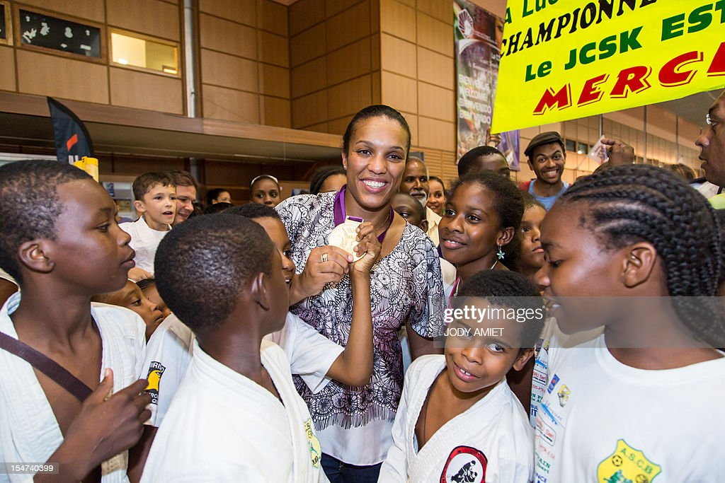 France's judo athlete and 2012 Olympic Games gold medalist Lucie Decosse (C) shows her medal as she is welcomed by supporters on October 24, 2012 in Cayenne, French overseas region of Guiana. The 30-year-old world champion beat German outsider Kerstin Thiele in the final of the women's -70kg judo contest match of the London 2012 Olympic Games on August 1, 2012.