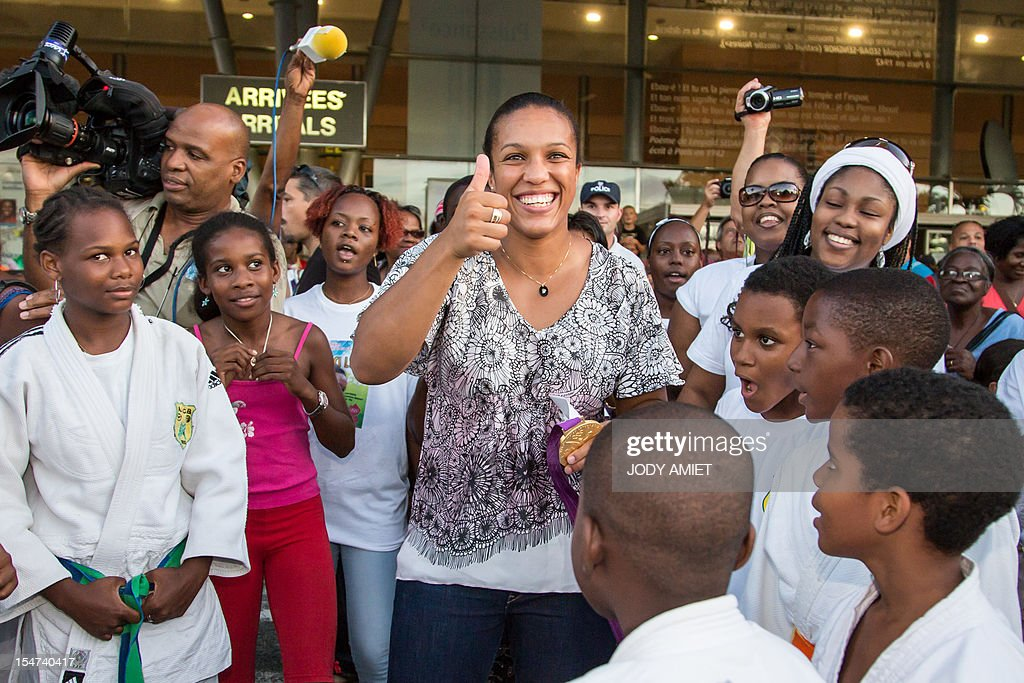 France's judo athlete and 2012 Olympic Games gold medalist Lucie Decosse (C) is welcomed by supporters on October 24, 2012 in Cayenne, French overseas region of Guiana. The 30-year-old world champion beat German outsider Kerstin Thiele in the final of the women's -70kg judo contest match of the London 2012 Olympic Games on August 1, 2012.