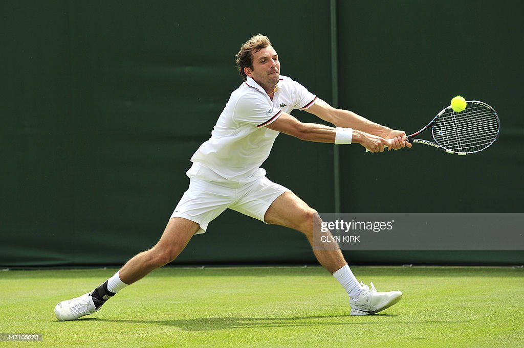 France's Julien Benneteau plays a double-handed backhand shot during his first round men's singles match against Luxembourg's Gilles Muller on the first day of the 2012 Wimbledon Championships tennis tournament at the All England Tennis Club in Wimbledon, southwest London, on June 25, 2012.