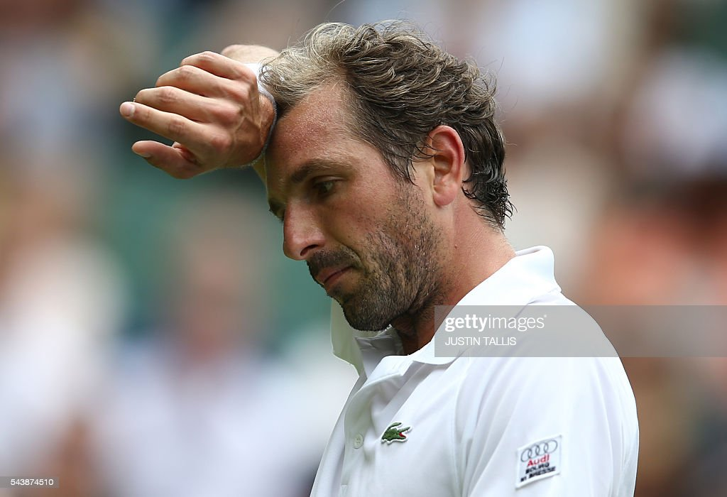 France's Julien Benneteau reacts while playing Japan's Kei Nishikori during their men's singles second round match on the fourth day of the 2016 Wimbledon Championships at The All England Lawn Tennis Club in Wimbledon, southwest London, on June 30, 2016. / AFP / JUSTIN