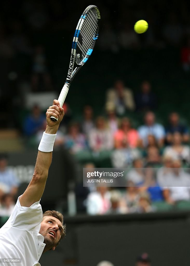 France's Julien Benneteau serves to Japan's Kei Nishikori during their men's singles second round match on the fourth day of the 2016 Wimbledon Championships at The All England Lawn Tennis Club in Wimbledon, southwest London, on June 30, 2016. / AFP / JUSTIN