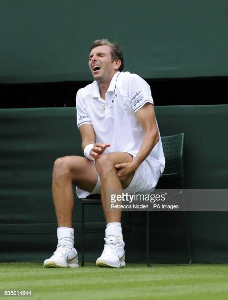 France's Julien Benneteau sits injured in his match against Serbia's Novak Djokovic during the 2009 Wimbledon Championships at the All England Lawn...
