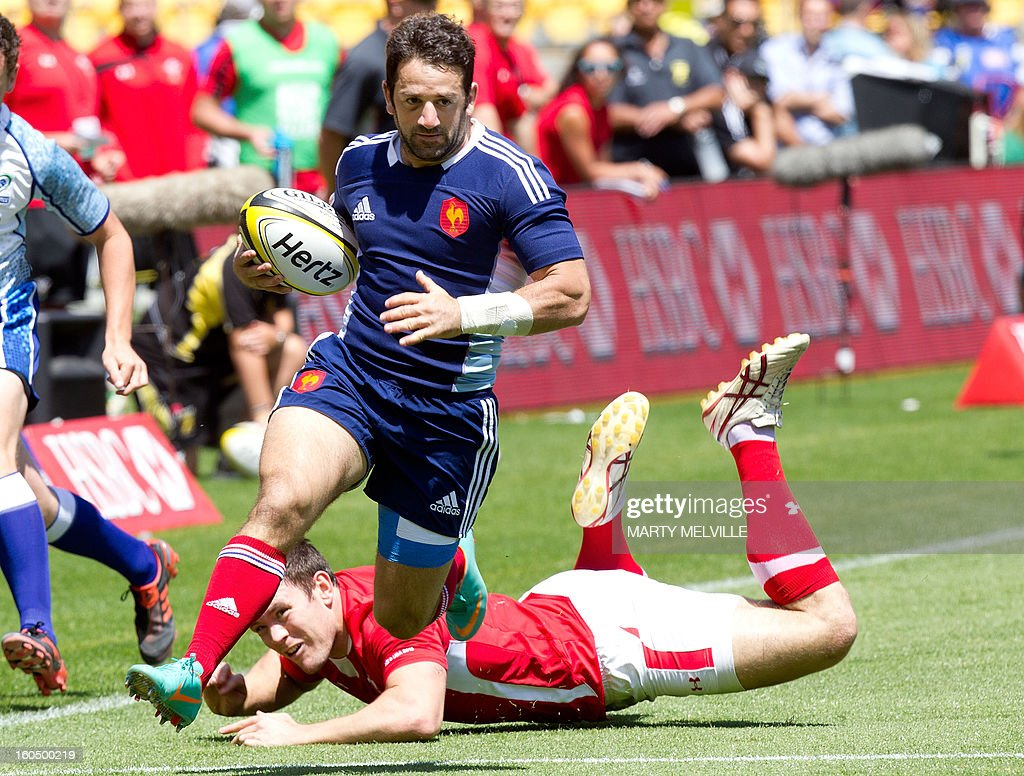 France's Julien Candelon runs out of a tackle by Wales's Adam Thomas during their Bowl Quarter Final at the Westpac Stadium on day two of the fourth leg of the IRB Rugby Sevens World Series in Wellington on February 2, 2013. AFP PHOTO / Marty MELVILLE