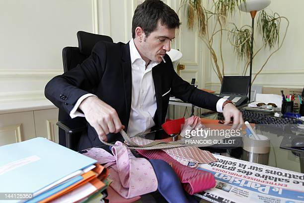 France's Junior Minister for Housing Benoist Apparu folds his ties as he packs his personal belongings on May 10 2012 in Paris at his ministry ahead...