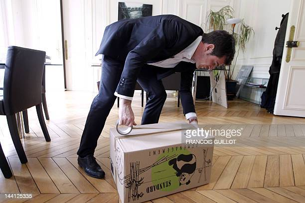 France's Junior Minister for Housing Benoist Apparu packs his personal belongings in a box on May 10 2012 in Paris at his ministry ahead of French...