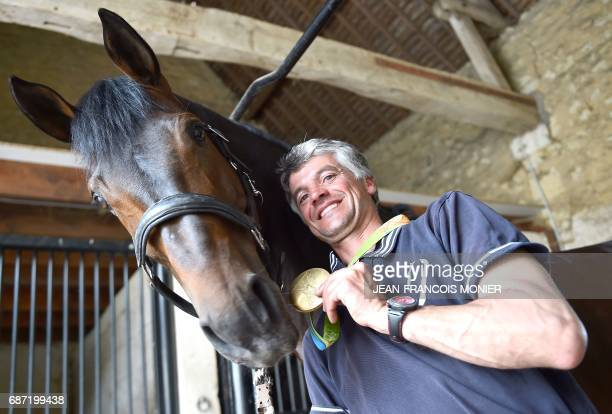 France's Karim Laghouag and his horse 'Entebbe de Hus' are pictured with the gold medal which he won at the Rio 2016 Olympic Games on May 15 2017 at...