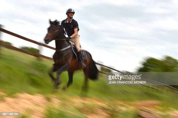France's Karim Laghouag rides his horse 'Entebbe de Hus' on which he won the gold medal in the event of Complete Competition by the French team at...