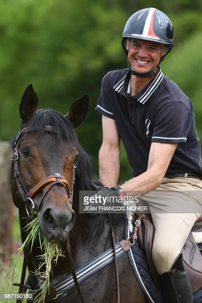 France's Karim Laghouag sits on his horse 'Entebbe de Hus' on which he won the gold medal in the event of Complete Competition by the French team at...