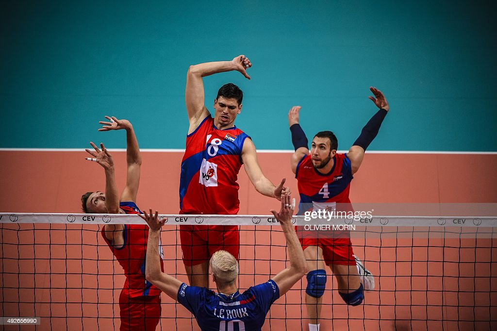 France's Kevin Le Roux faces Serbia's Marko Podrascanin and Serbia's Nemanja Peztric during the quarterfinal volleyball match France vs Serbia at the...