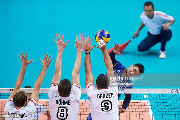 France's Kevin Tillie attacks against Germany'Dirk Westphal and Marcus Boehme and Gyorgy Grozer during the FIVB World Championships match between...