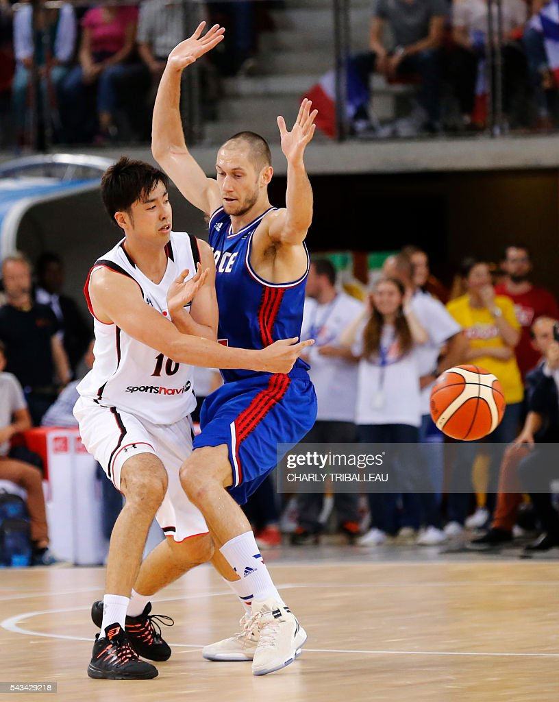 France's Kim Tillie (R) vies for the ball with Japan's Kosuke Takeuchi (L) during the basketball match between France and Japan at the Kindarena hall in Rouen on June 28, 2016. / AFP / CHARLY