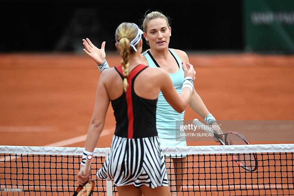 France's Kristina Mladenovic (L) shakes hands with Hungary's Timea Babos after winning their women's second round match at the Roland Garros 2016 French Tennis Open in Paris on May 26, 2016. / AFP / MARTIN