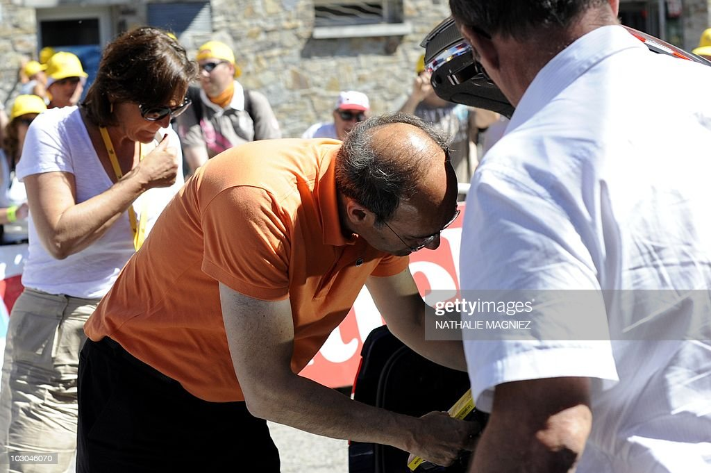 France's Labour Minister Eric Woerth (C), flanked by his wife Florence (L) looks inside the Tour de France official car's storage compartment at the finish line during the 184,5 km and 14th stage of the 2010 Tour de France cycling race run between Revel and Ax-Trois-Domaines, southern France in Pyrenees region on July 18, 2010. Woerth faced yesterday fresh pressure in a cash scandal over France's richest woman after police questioned one of her advisers, according to details published by a newspaper.