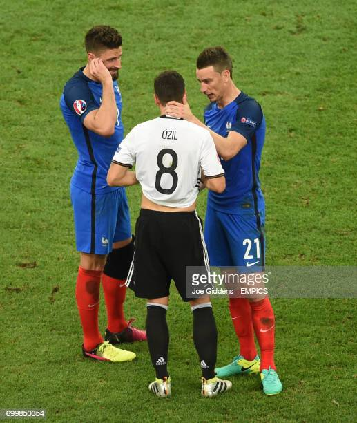 France's Laurent Koscielny and Olivier Giroud console Arsenal teammate Germany's Mesut Ozil