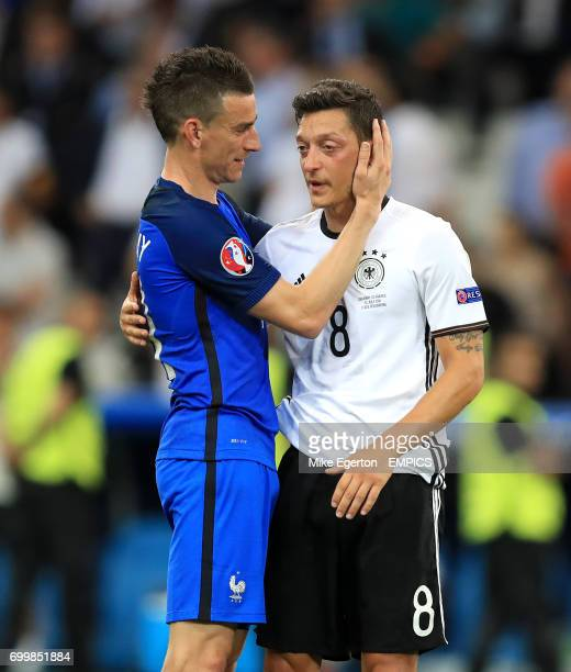France's Laurent Koscielny consoles Germany's Mesut Ozil after the game