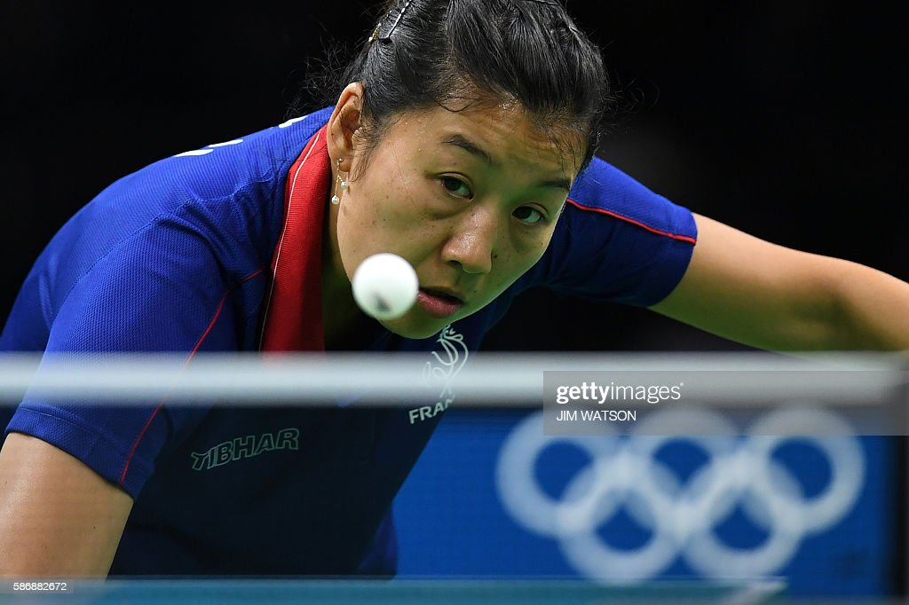 France's Li Xue eyes the ball in her women's singles qualification round table tennis match at the Riocentro venue during the Rio 2016 Olympic Games in Rio de Janeiro on August 7, 2016. / AFP / Jim WATSON