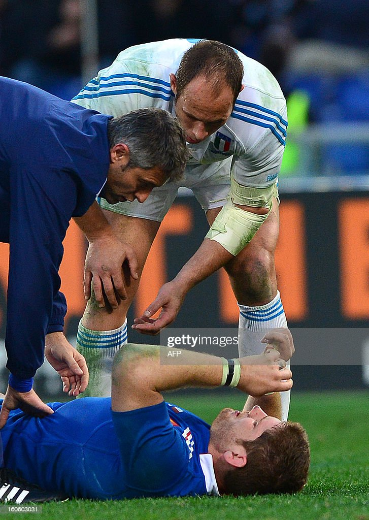 France's lock and captain Pascal Pape lies on the pitch as Italy's N°8 and captain Sergio Parisse looks at him during the Six Nations international rugby union match Italy vs France in Rome's Olimpic Stadium on February 3, 2013. Italy defeated France 23-18. AFP PHOTO / GABRIEL BOUYS