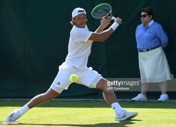 France's Lucas Pouille returns against Poland's Jerzy Janowicz during their men's singles second round match on the third day of the 2017 Wimbledon...