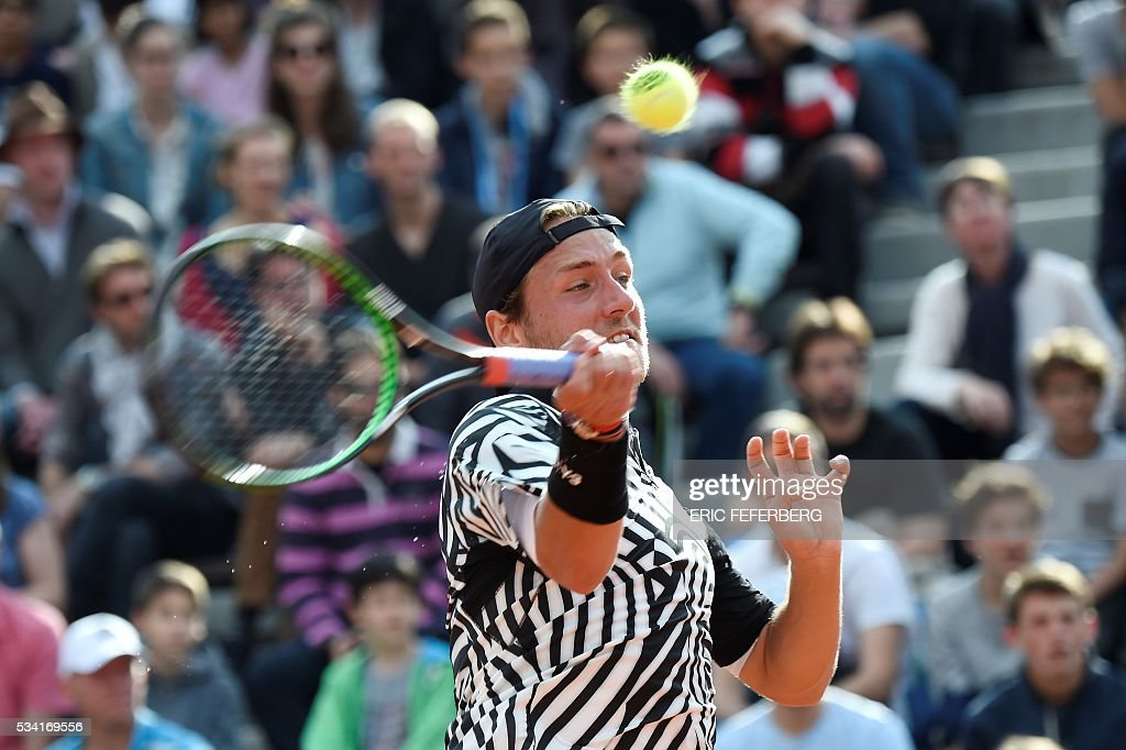France's Lucas Pouille returns the ball to Slovakia's Andrej Martin during their men's second round match at the Roland Garros 2016 French Tennis Open in Paris on May 25, 2016. / AFP / Eric FEFERBERG