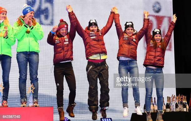 France's Marie Dorin Haber Justine Braisaz Celia Aymonier and Anais Chevalier celebrate on the podium of the 2017 IBU World Championships Biathlon...