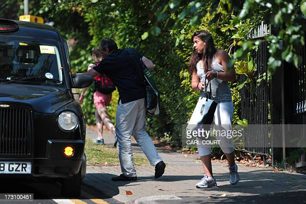 France's Marion Bartoli and her father Walter arrive in a taxi to attend a press conference in southwest London on July 7 2013 the day after winning...