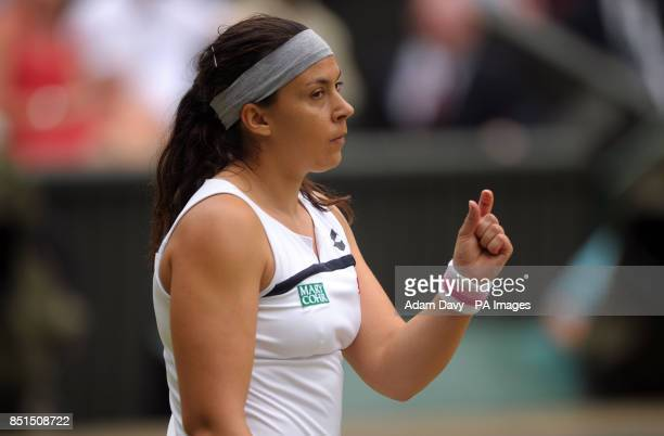 France's Marion Bartoli reacts to a line call during her match against Belgium's Kirsten Flipkens during day ten of the Wimbledon Championships at...