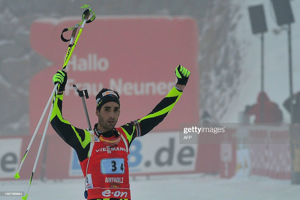 France's Martin Fourcade celebrates as he crosses in victory the finish line of the 4x7,5 kilometers' relay race of the men's biathlon World Cup race on January 20, 2013 in Antholz-Anterselva. France team won ahead of Russia and Austria.