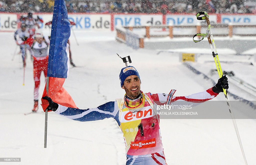 France's Martin Fourcade celebrates as he crosses the finish line to place first during the men's 15 km mass start event of the IBU Biathlon Word Cup in the Siberian city of Khanty-Mansiysk, on March 17, 2013. Fourcade took first place ahead of Austria's Dominik Landertinger and Norway's Emil Hegle Svendsen.