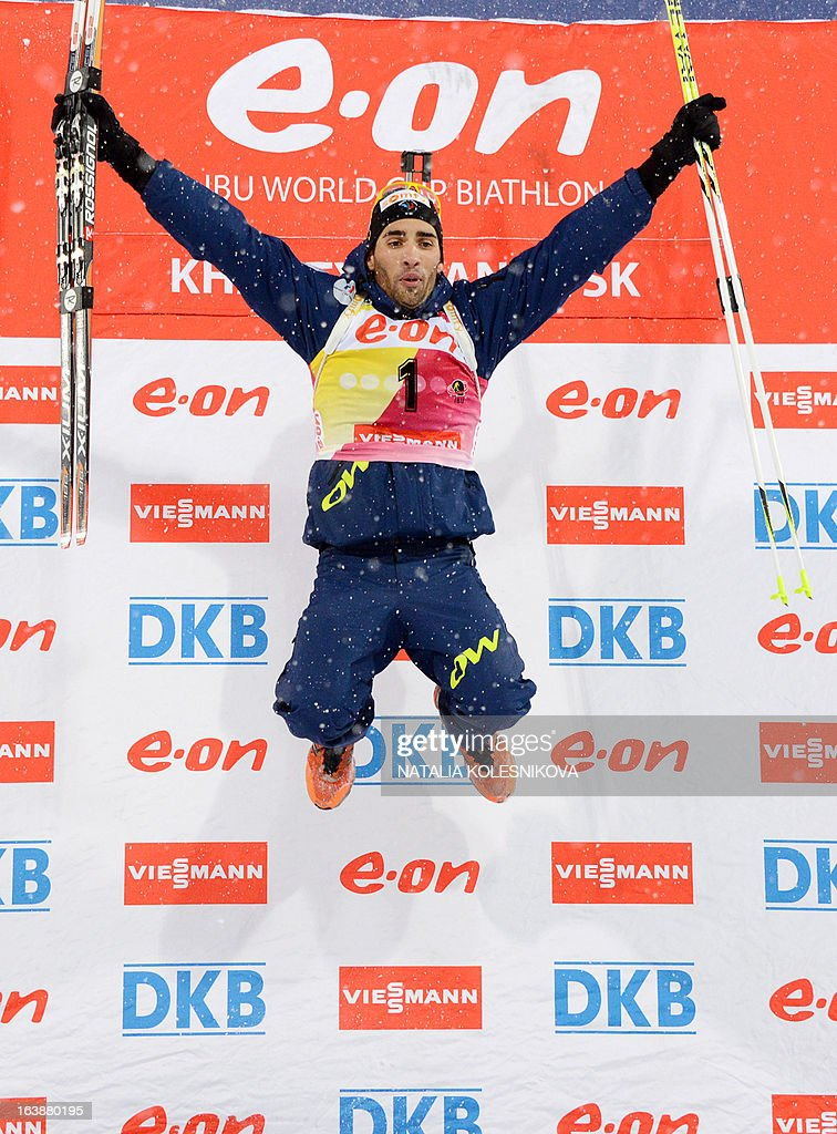 France's Martin Fourcade celebrates on the podium after winning the men's 15 km mass start event of the IBU Biathlon Word Cup in the Siberian city of Khanty-Mansiysk, on March 17, 2013. Fourcade took the first place ahead of Austria's Dominik Landertinger and Norway's Emil Hegle Svendsen. AFP PHOTO/NATALIA KOLESNIKOVA