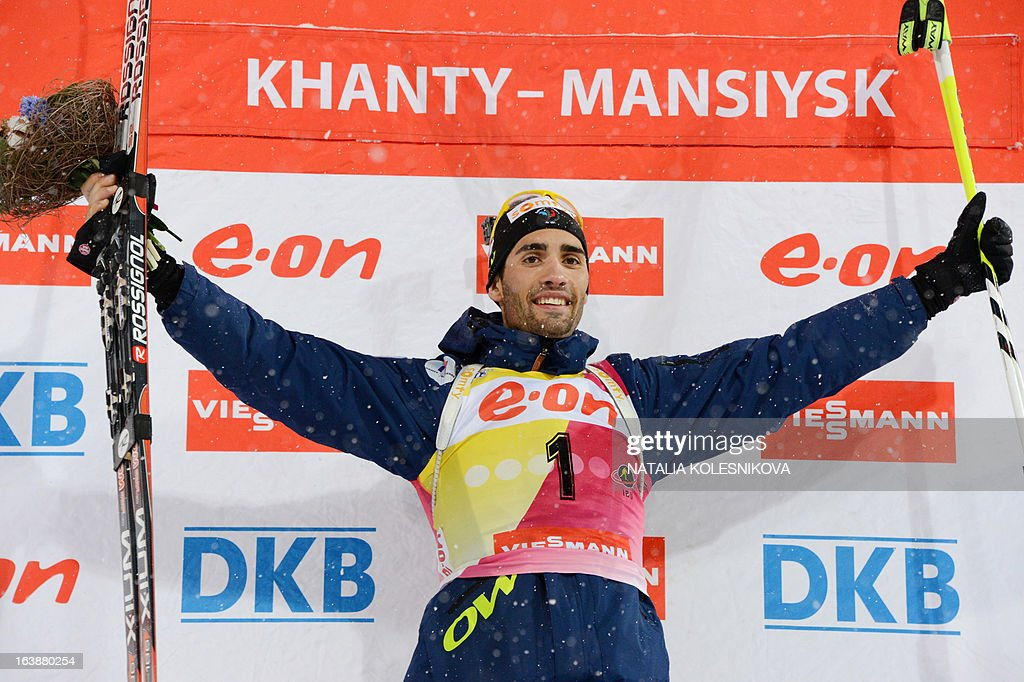 France's Martin Fourcade celebrates on the podium after winning the men's 15 km mass start event of the IBU Biathlon Word Cup in the Siberian city of Khanty-Mansiysk, on March 17, 2013. Fourcade took first place ahead of Austria's Dominik Landertinger and Norway's Emil Hegle Svendsen.